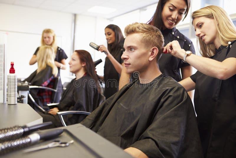 Profesor Helping Students Training a hacer peluqueros fotos de archivo