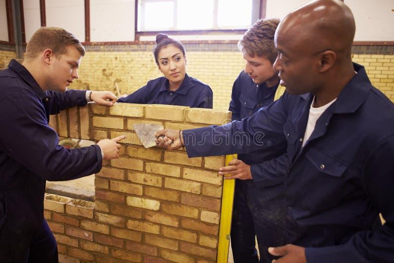 Profesor Helping Students Training a ser constructores imagen de archivo