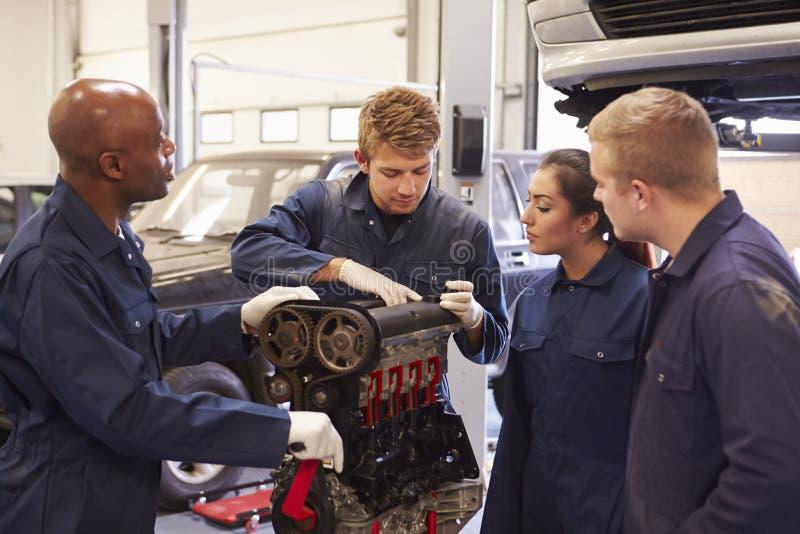 Profesor Helping Students Training a ser mecánicos de coche imagen de archivo