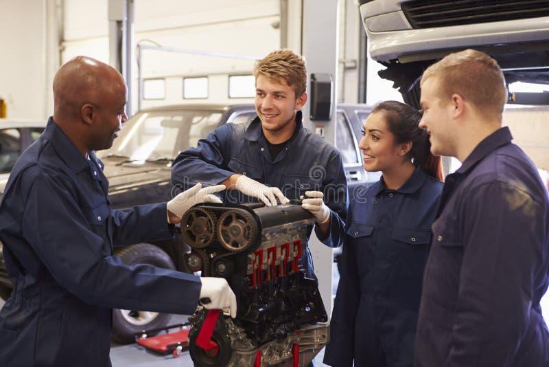 Profesor Helping Students Training a ser mecánicos de coche imágenes de archivo libres de regalías