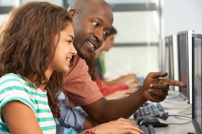 Profesor Helping Students Working en los ordenadores en sala de clase imagenes de archivo