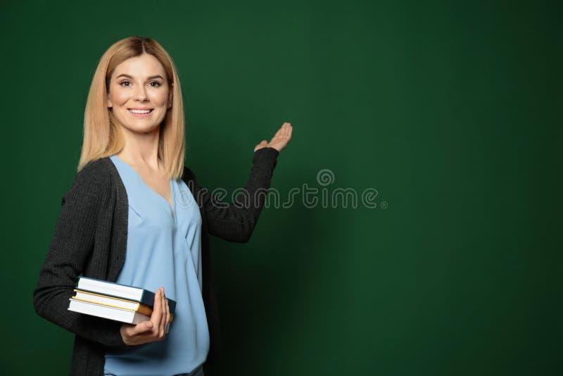 Profesor hermoso con los libros que señala en la pizarra imagen de archivo