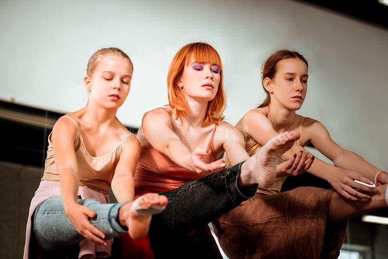 Profesor hermoso de la danza con el pelo rojo y sus los estudiantes que bailan en el estudio foto de archivo
