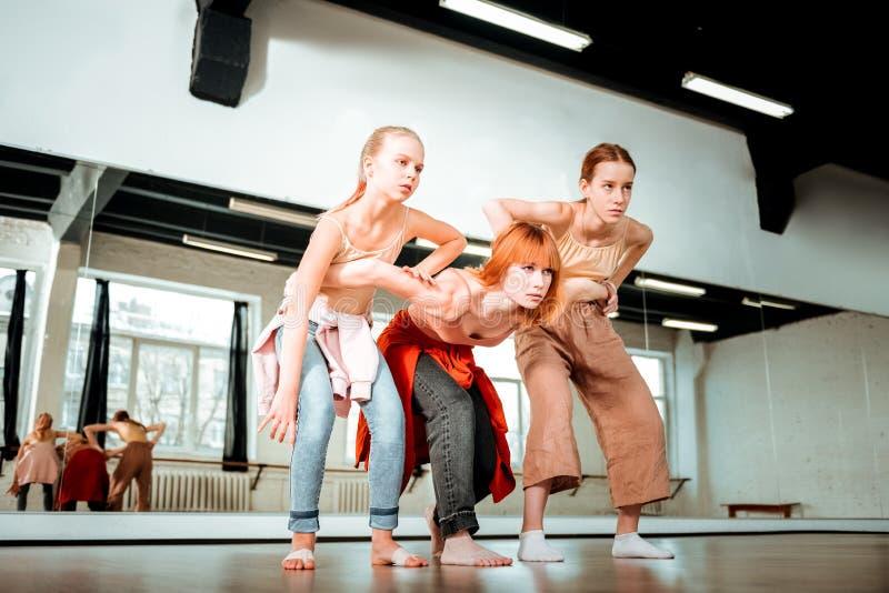 Profesor hermoso de la danza con el pelo rojo y sus los estudiantes que estiran sus piernas fotografía de archivo