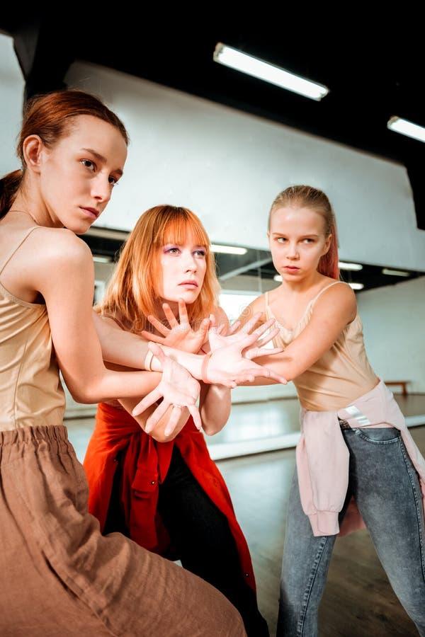 Profesor hermoso de la danza con el pelo rojo y sus los estudiantes que hacen estirar del brazo fotos de archivo