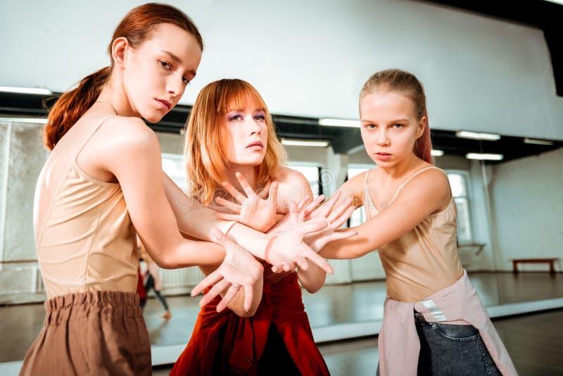 Profesor hermoso de la danza con el pelo rojo y sus los estudiantes que parecen artísticos fotografía de archivo libre de regalías