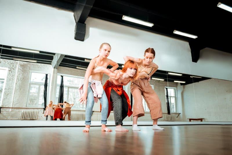 Profesor hermoso de la danza con el pelo rojo y sus los estudiantes que parecen serios imagenes de archivo