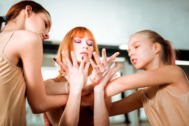 Profesor hermoso de la danza con el pelo rojo y sus los estudiantes que trabajan en movimientos de las manos foto de archivo