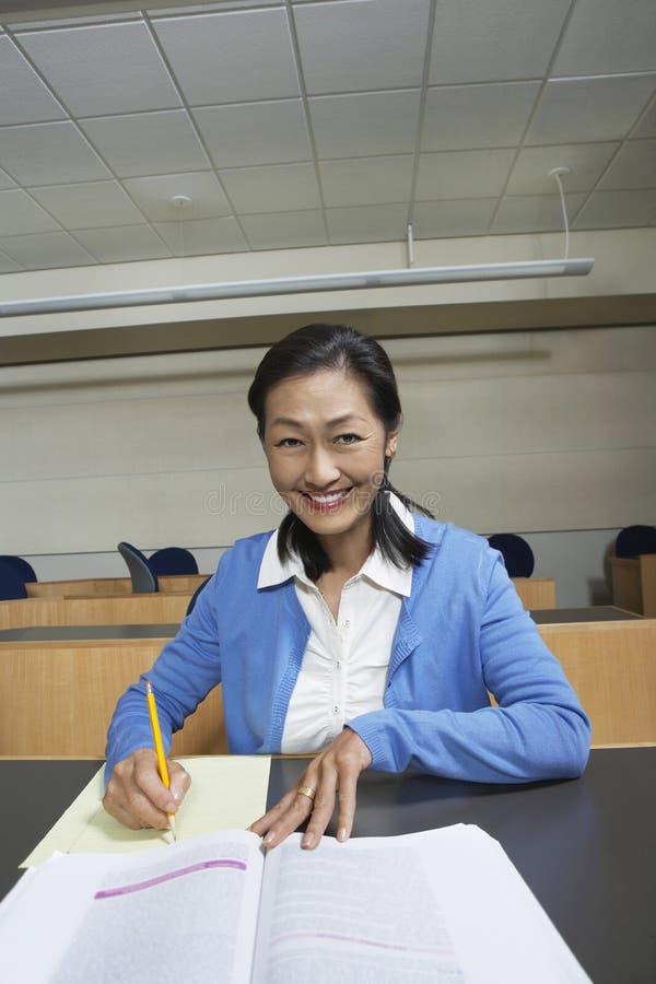 Profesor Jotting Down Notes en sala de clase imagen de archivo libre de regalías