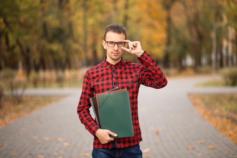 Profesor joven en los vidrios que sostienen carpetas en parque del otoño foto de archivo libre de regalías