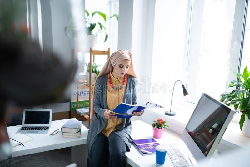 Profesor joven moderno que siente ocupado mientras que libro de lectura foto de archivo libre de regalías