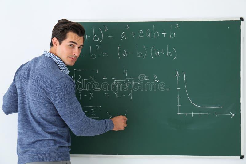 Profesor joven que escribe fórmulas de la matemáticas en la pizarra foto de archivo libre de regalías