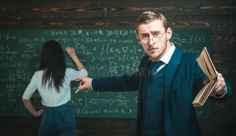 Profesor joven que señala en el tablero mientras que sostiene el libro en mano recta Profesor joven que da explicaciones a los es fotografía de archivo libre de regalías
