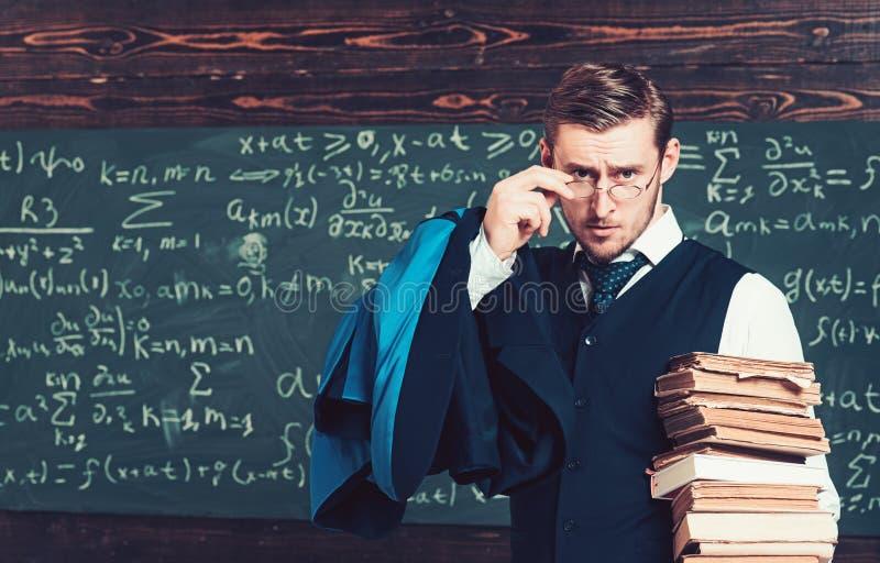 Profesor joven que sostiene la pila de libros que miran sobre sus vidrios Escolar del aristócrata en universidad de élite foto de archivo
