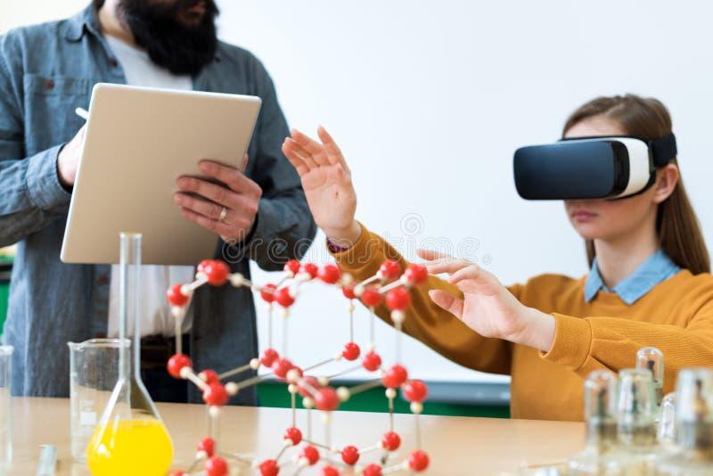 Profesor joven que usa los vidrios de la realidad virtual y la presentación 3D para enseñar a estudiantes en clase de química Edu fotografía de archivo libre de regalías