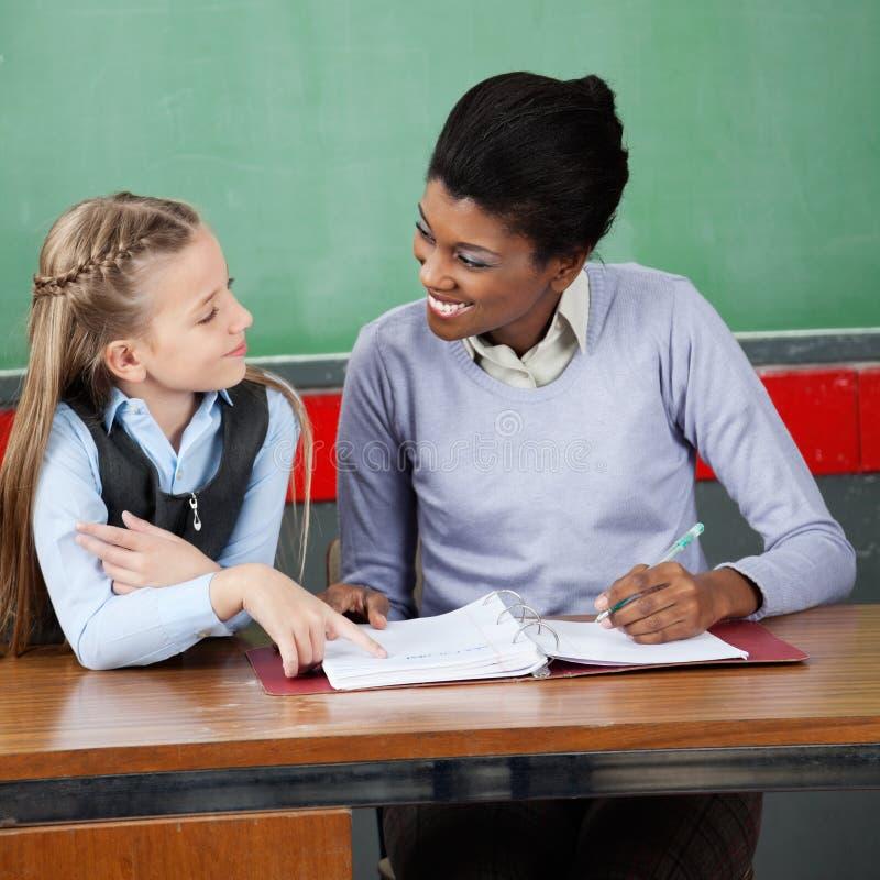 Profesor Looking At Schoolgirl en el escritorio imagen de archivo