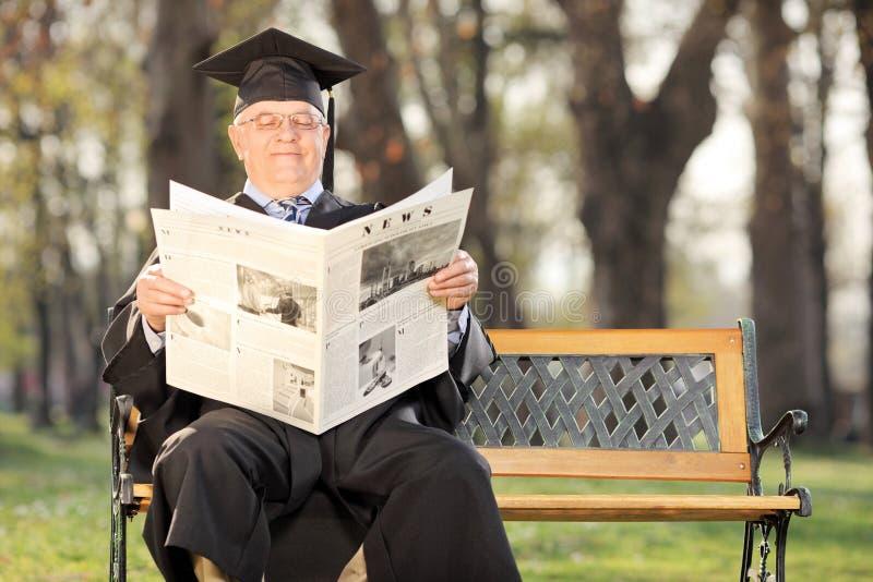Profesor maduro de la universidad que lee las noticias en parque imágenes de archivo libres de regalías