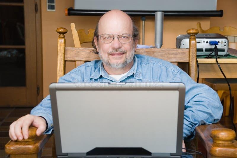 Profesor mayor con la computadora portátil fotografía de archivo