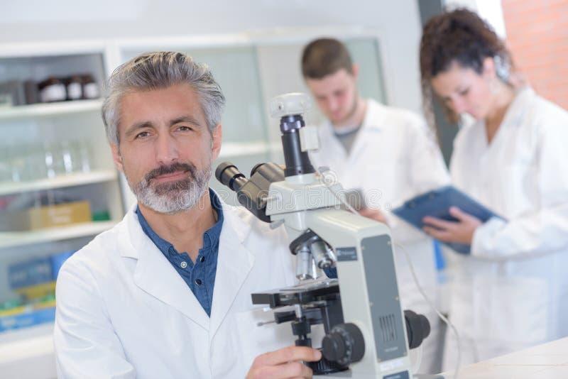 Profesor mayor de la química en laboratorio con los colegas imagen de archivo