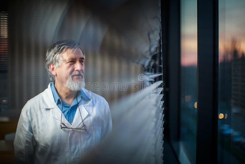 Profesor mayor de la química por una ventana de la sala de clase imagenes de archivo