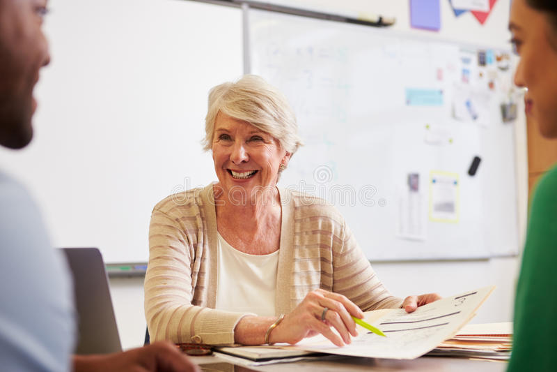 Profesor mayor en el escritorio que habla con los estudiantes de la enseñanza para adultos fotografía de archivo libre de regalías