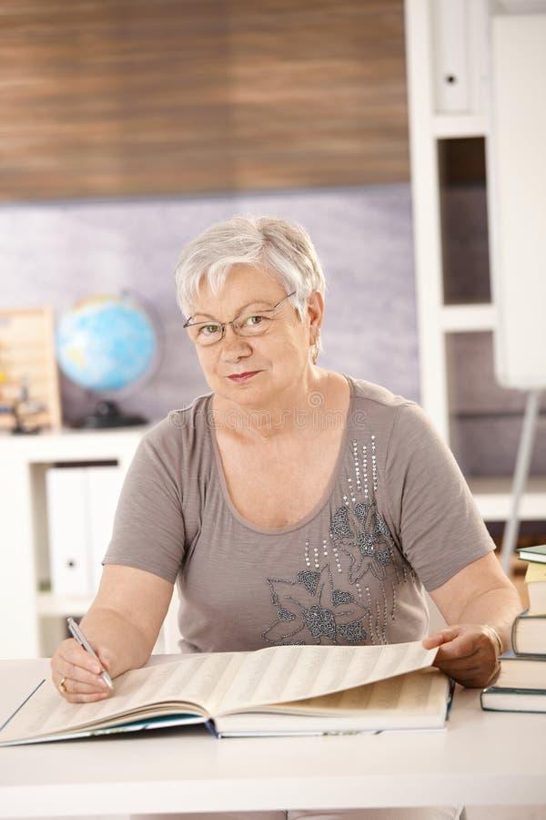 Profesor mayor en la escuela que mira a niños foto de archivo