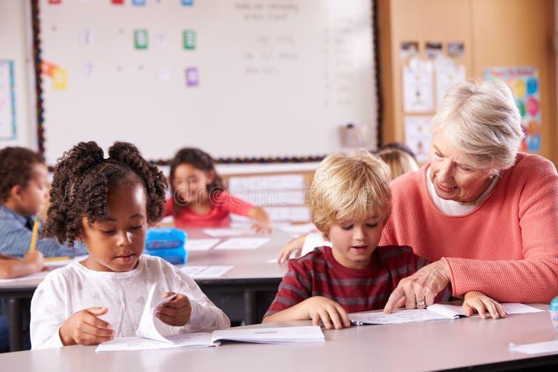 Profesor mayor que ayuda al alumno de la escuela primaria en clase fotos de archivo libres de regalías