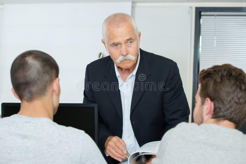Profesor mayor y 2 muchachos de los estudiantes con el ordenador imagen de archivo