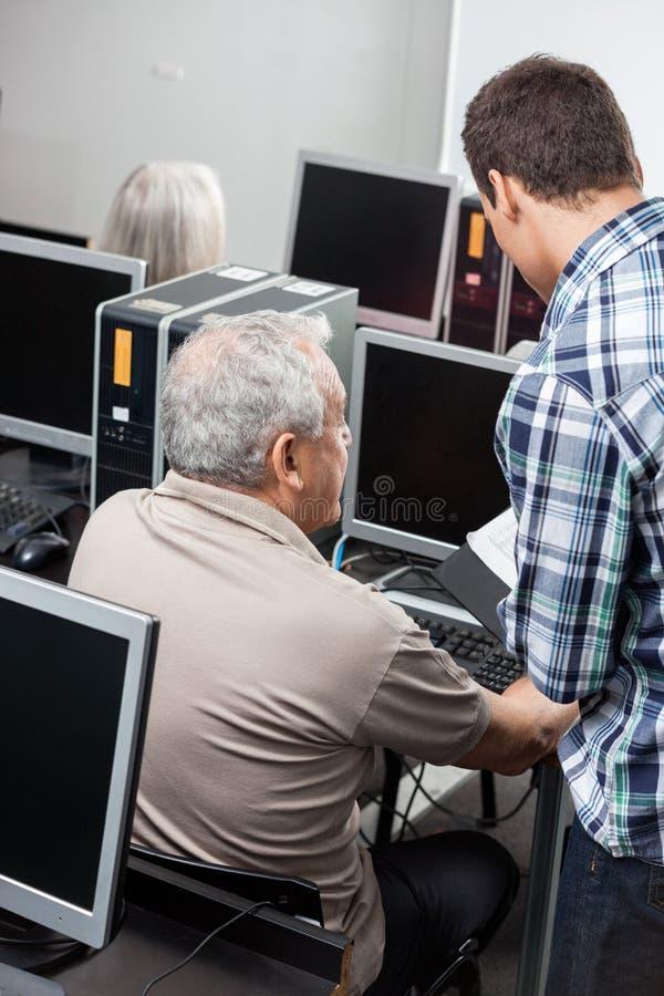 Profesor particular Assisting Senior Man al usar el ordenador en la sala de clase fotos de archivo