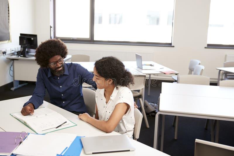 Profesor particular cuota de Giving Female Student uno a uno de la escuela secundaria en el escritorio en sala de clase fotografía de archivo