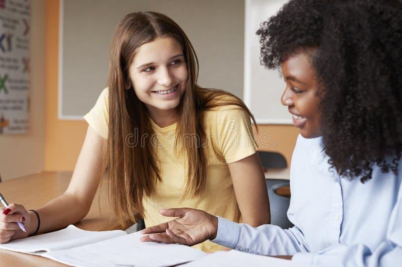 Profesor particular cuota de Giving Female Student uno a uno de la High School secundaria en el escritorio imagenes de archivo
