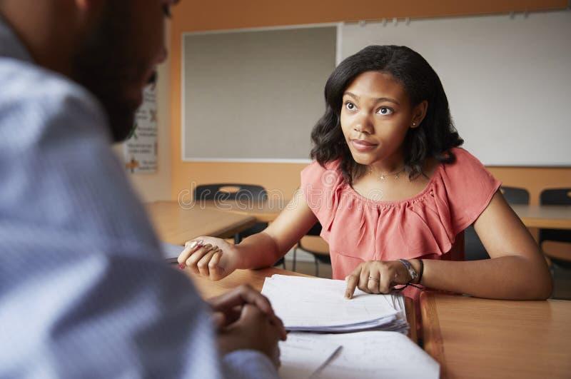 Profesor particular cuota de Giving Female Student uno a uno de la High School secundaria en el escritorio imagen de archivo