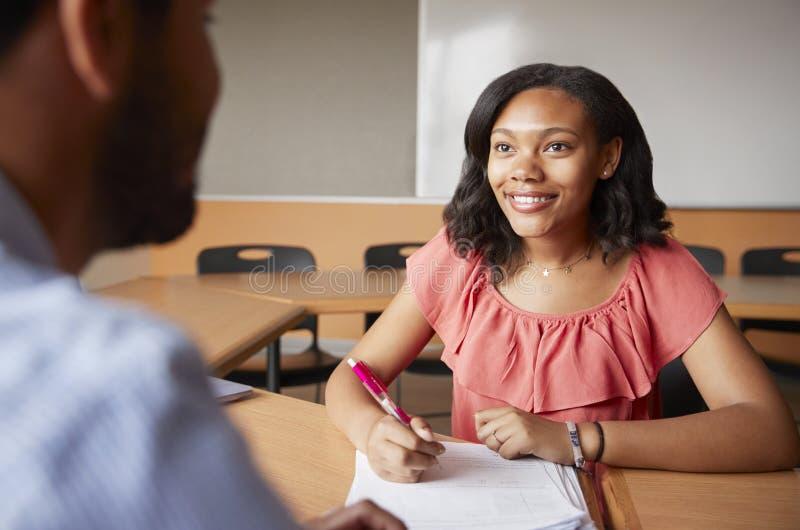Profesor particular cuota de Giving Female Student uno a uno de la High School secundaria en el escritorio imágenes de archivo libres de regalías