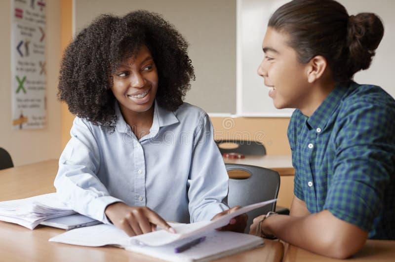 Profesor particular cuota de Giving Male Student uno a uno de la High School secundaria en el escritorio fotografía de archivo