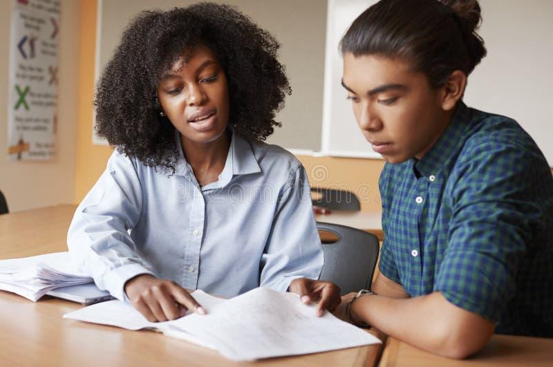 Profesor particular cuota de Giving Male Student uno a uno de la High School secundaria en el escritorio foto de archivo