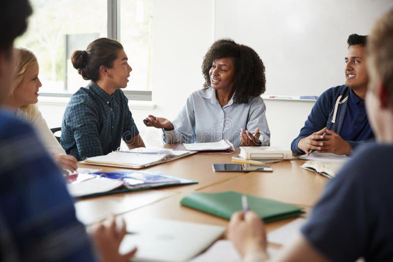 Profesor particular de sexo femenino Sitting At Table de la High School secundaria con los alumnos que enseñan a la clase de la m imagenes de archivo