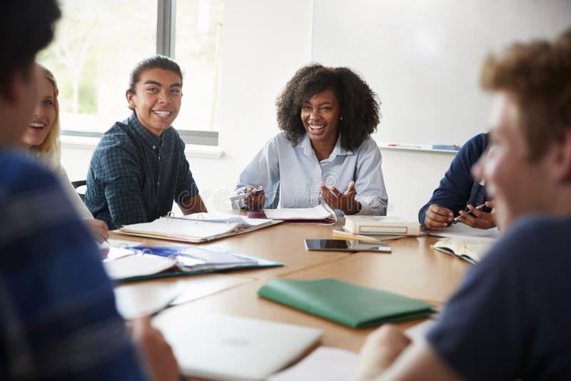 Profesor particular de sexo femenino Sitting At Table de la High School secundaria con los alumnos que enseñan a la clase de la m fotos de archivo libres de regalías