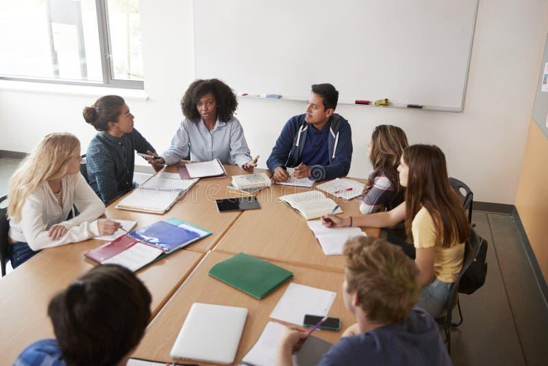 Profesor particular de sexo femenino Sitting At Table de la High School secundaria con los alumnos que enseñan a la clase de la m imágenes de archivo libres de regalías