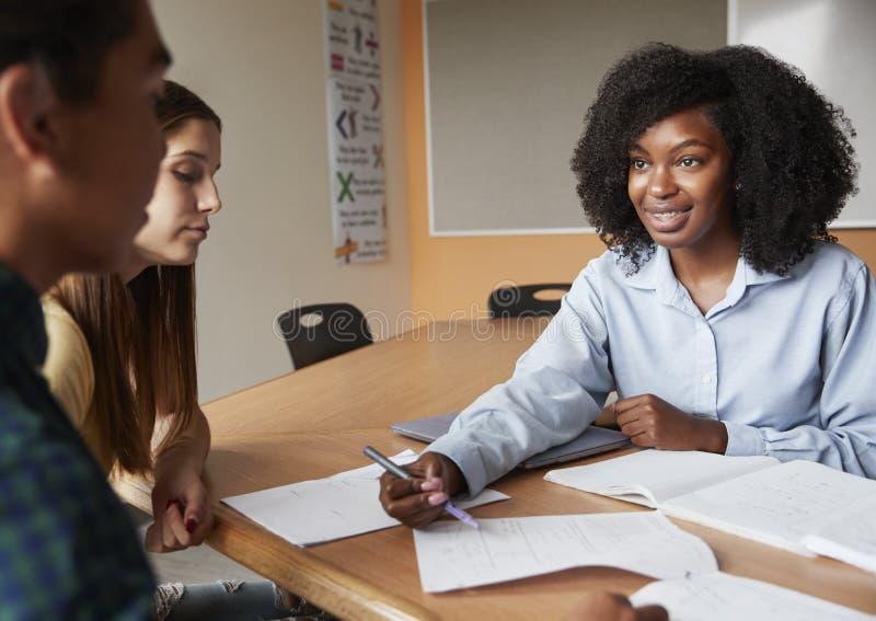 Profesor particular de sexo femenino With Two Students de la High School secundaria en el escritorio en seminario foto de archivo