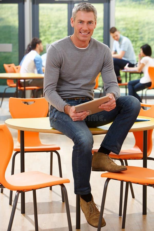 Profesor particular de sexo masculino Sitting In Classroom con la tableta de Digitaces imagen de archivo