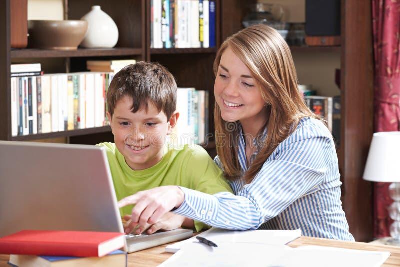Profesor particular Helping Boy Studying en casa foto de archivo