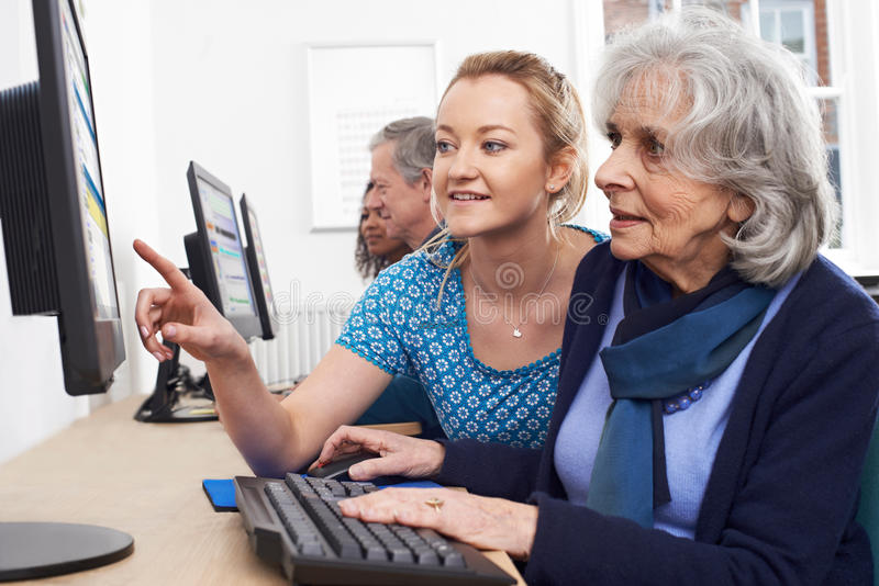 Profesor particular Helping Senior Woman en clase del ordenador foto de archivo