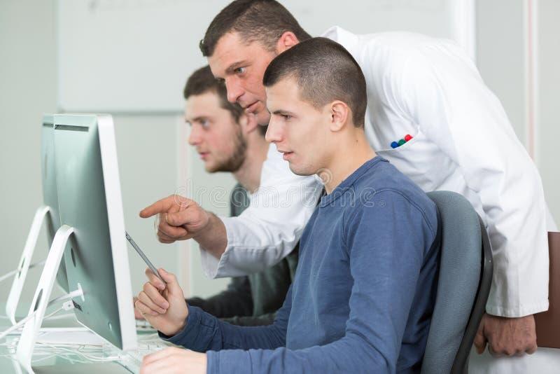 Profesor particular y estudiantes jovenes en clase computacional fotografía de archivo libre de regalías