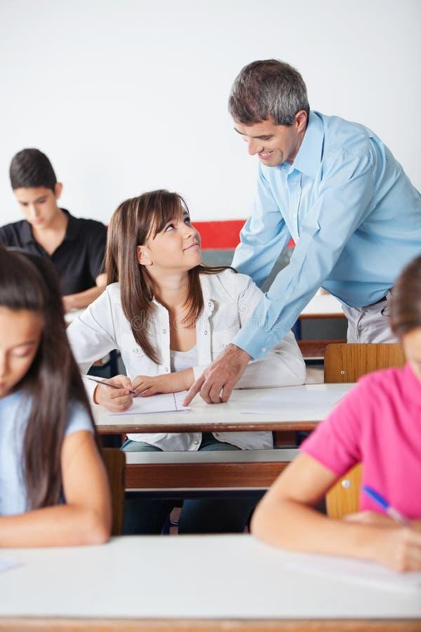 Profesor Pointing At Paper mientras que estudiante Looking fotografía de archivo