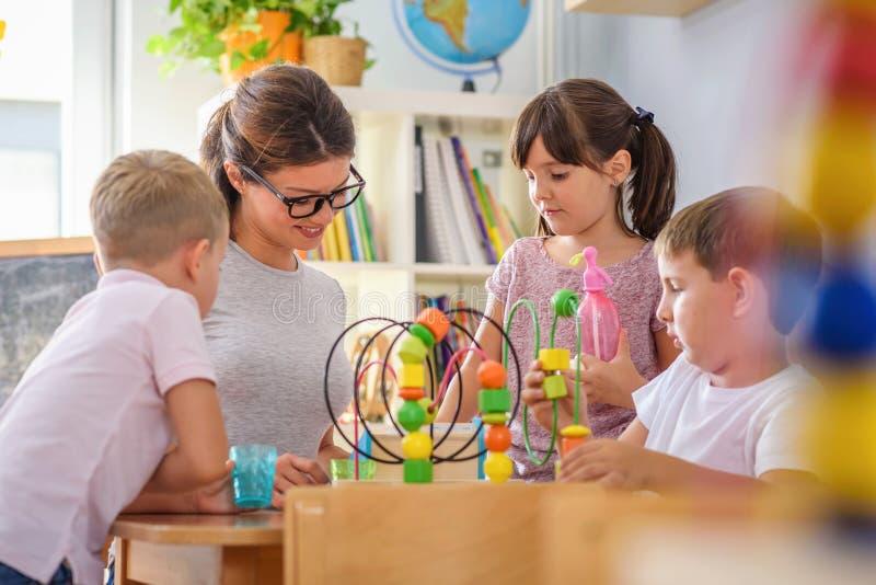 Profesor preescolar con los niños que juegan con los juguetes didácticos coloridos en la guardería imagenes de archivo