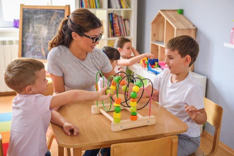 Profesor preescolar con los niños que juegan con los juguetes didácticos coloridos en la guardería foto de archivo