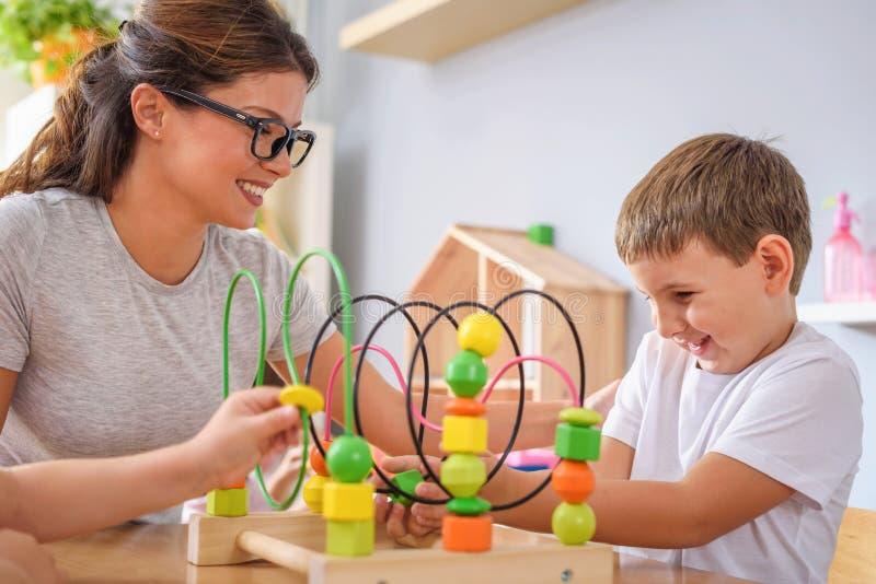 Profesor preescolar con los niños que juegan con los juguetes didácticos coloridos en la guardería fotos de archivo libres de regalías