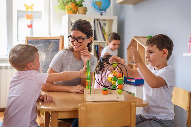 Profesor preescolar con los niños que juegan con los juguetes didácticos coloridos en la guardería imagen de archivo