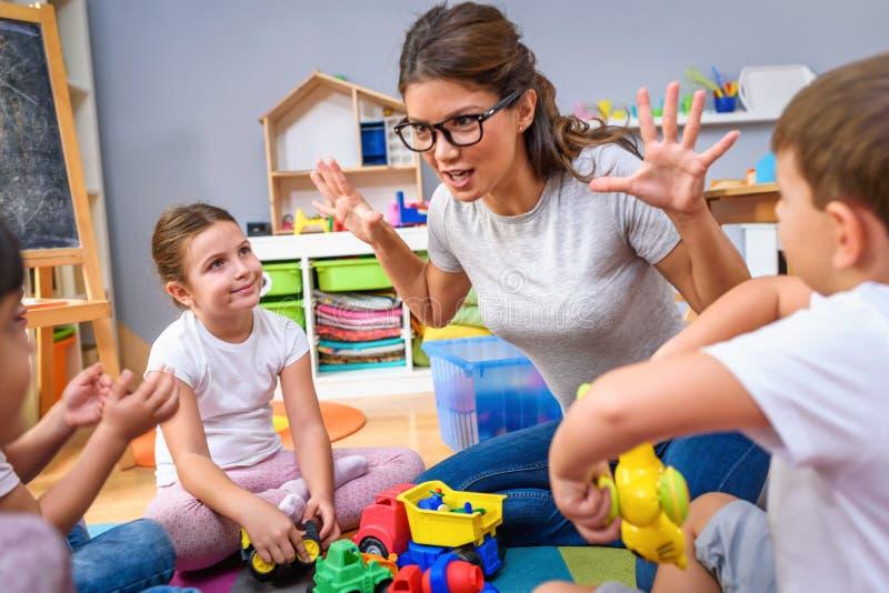 Profesor preescolar que habla con el grupo de niños que se sientan en un piso en la guardería fotografía de archivo libre de regalías