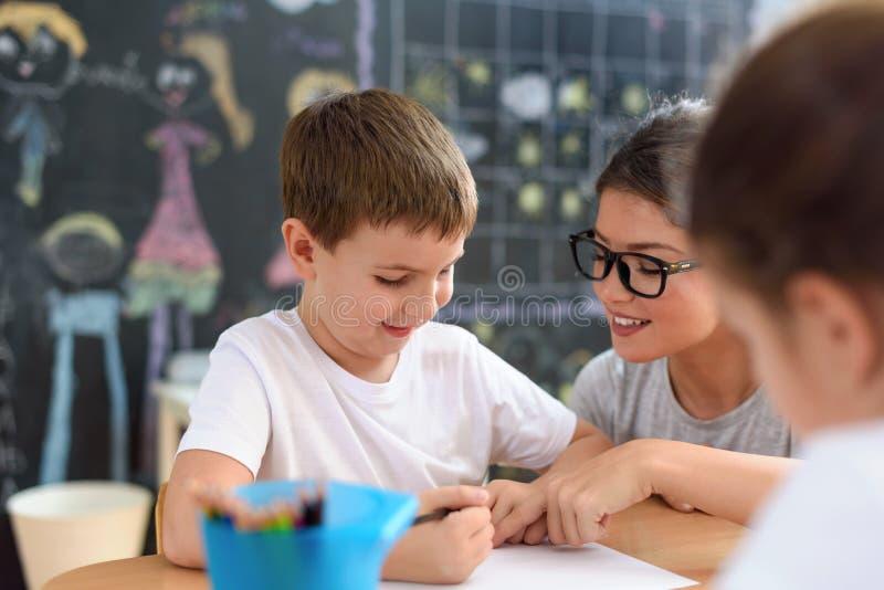 Profesor preescolar que mira al niño elegante que aprende escribir y dibujar imagen de archivo